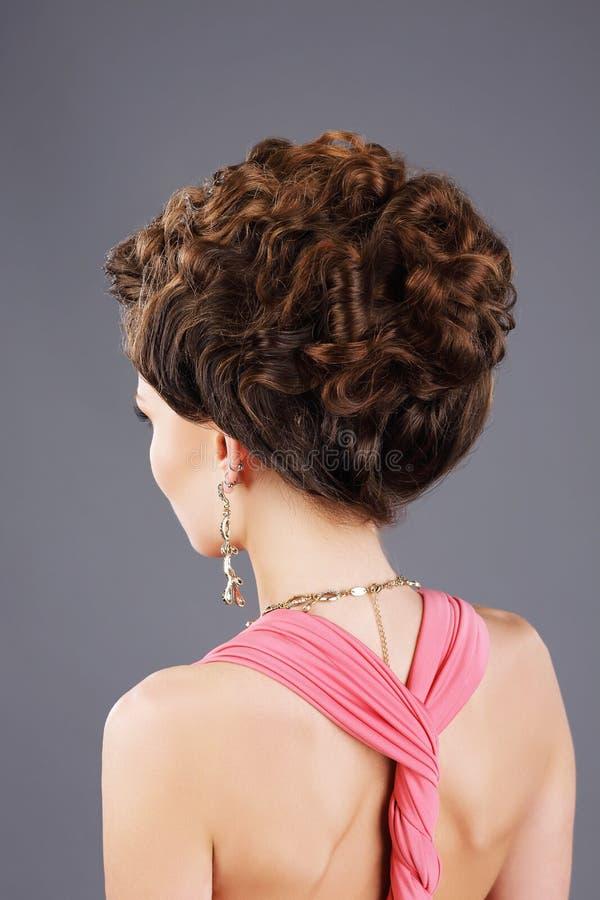 Burrigt hår Bakre sikt av den bruna hårkvinnan med den festliga frisyren royaltyfri foto