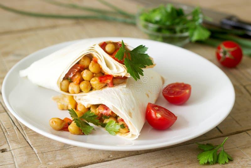 Burrito ή shawurma με chickpeas, τις ντομάτες και το μαϊντανό σε ένα ελαφρύ πιάτο στοκ φωτογραφία με δικαίωμα ελεύθερης χρήσης