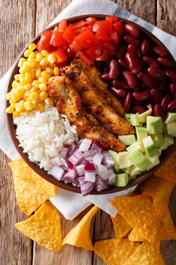 Burrito bowl with chicken grilled, rice and vegetables close-up. Vertical top view, Mexican style stock images