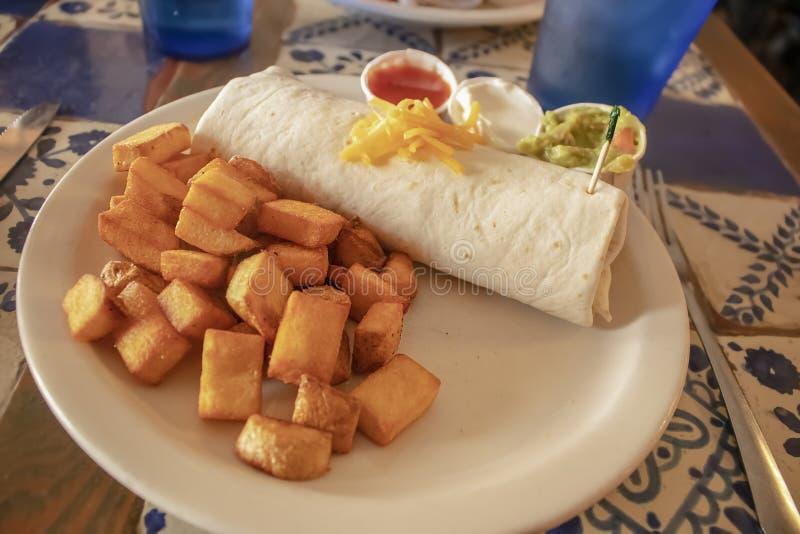 Burrito delicioso del desayuno y patatas fritas cubicadas en una placa en una tabla de la teja en un resturant imágenes de archivo libres de regalías