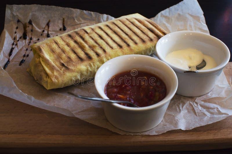 Burrito en el papel con salsa imágenes de archivo libres de regalías