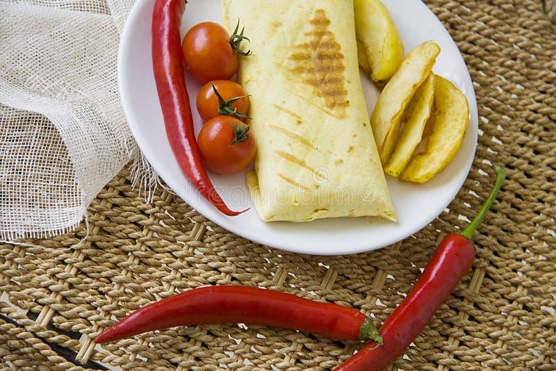 Burrito en gebraden die aardappel met tomaat en Spaanse peper wordt gediend royalty-vrije stock fotografie