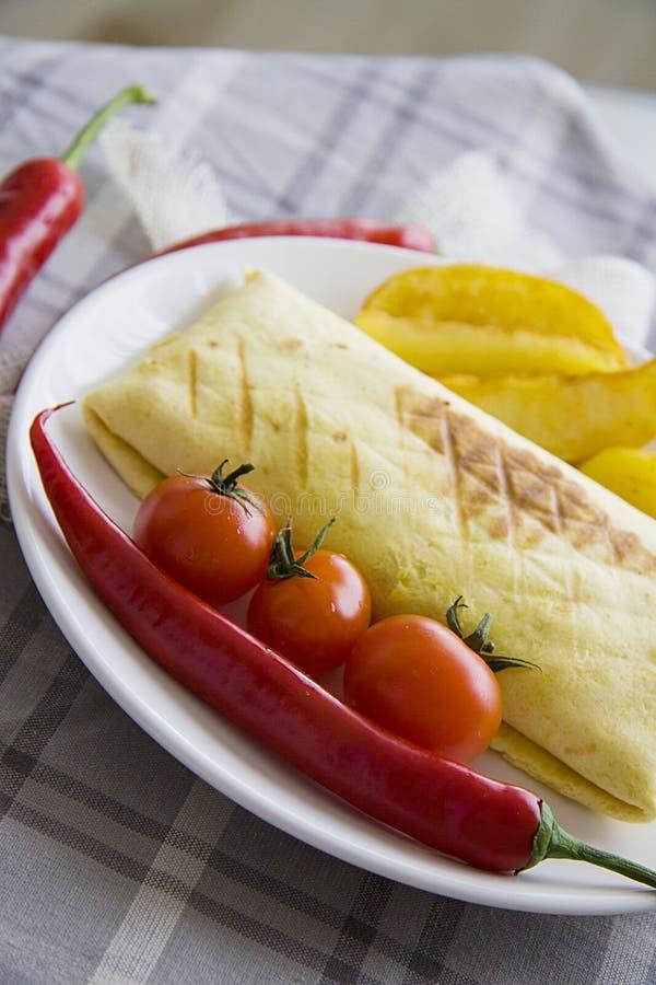 Burrito en gebraden die aardappel met tomaat en Spaanse peper wordt gediend royalty-vrije stock afbeeldingen