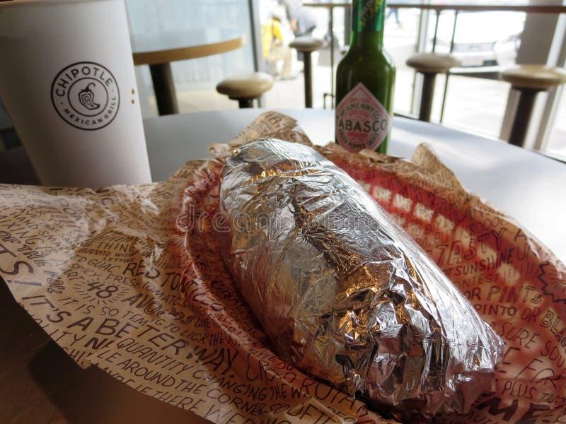Burrito envolvido com bebida e verde tabasco no Chipotle foto de stock royalty free