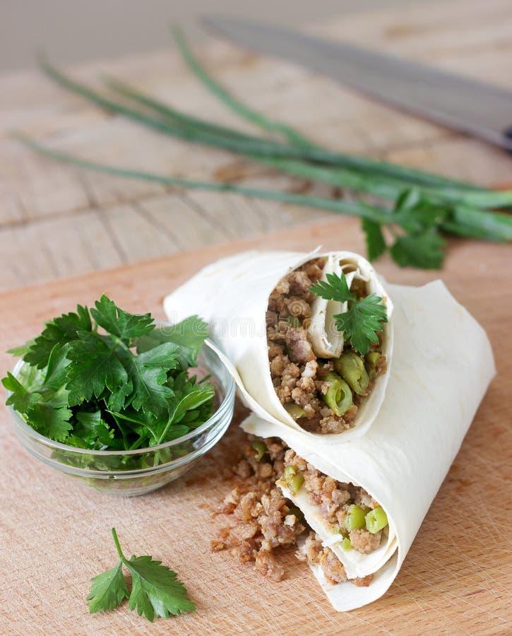 Burrito lub shawurma z minced fasolkami szparagowymi na drewnianej desce i mięsem fotografia royalty free