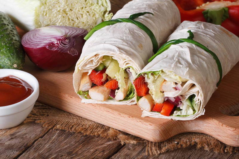 Burrito med höna och grönsaker med ingredienser som är horisontal royaltyfria bilder