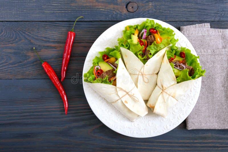 Burrito med huggit av kött, avokado, grönsaker, varm peppar på en platta på en mörk träbakgrund royaltyfri fotografi
