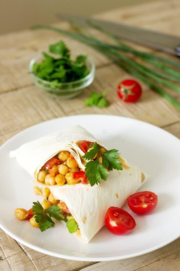 Burrito o shawurma con i ceci, i pomodori ed il prezzemolo su un piatto leggero immagine stock