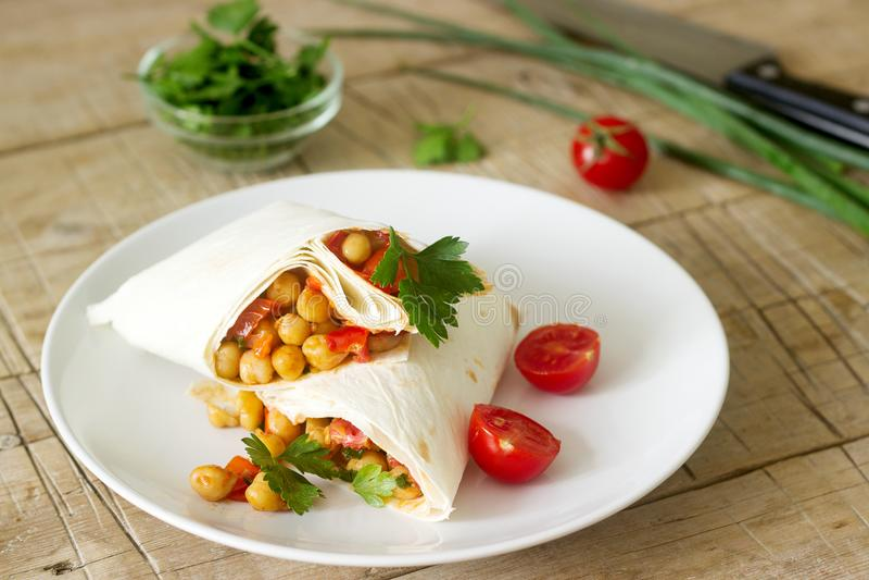 Burrito o shawurma con i ceci, i pomodori ed il prezzemolo su un piatto leggero fotografia stock