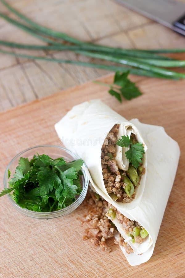 Burrito oder shawurma mit Hackfleisch und grünen Bohnen auf einem hölzernen Brett lizenzfreie stockbilder