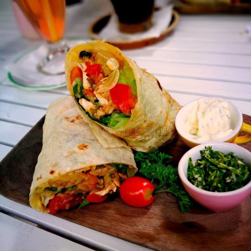 Burrito opakunki z wołowiną i warzywami na drewnianym prostokątnym talerzu Wo?owiny burrito, meksyka?ski jedzenie obraz royalty free