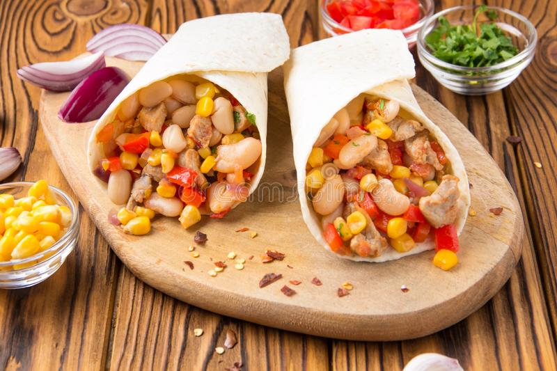 Burrito in tartilla with meat, vegetables, white beans, red pepper, corn. Delicious lunch, Mexican food, homemade snack stock image