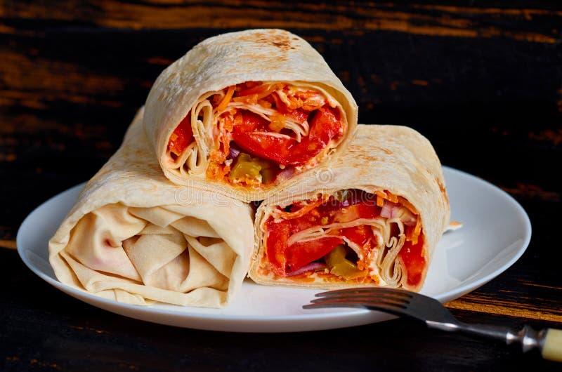 Burrito végétarien avec les légumes frais du plat blanc décoré de la fourchette argentée sur le fond en bois noir de cuisine photo libre de droits