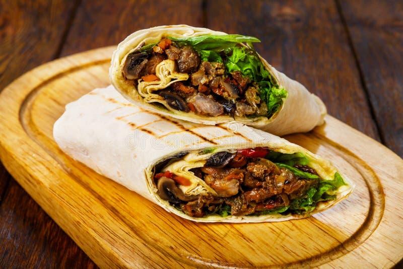 Burritos con carne di maiale, i funghi e le verdure allo scrittorio di legno immagine stock