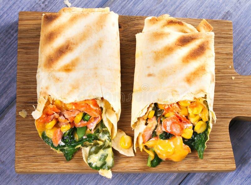 Burritos de los salmones, de la espinaca, del queso cheddar y del maíz Abrigos de los pescados foto de archivo