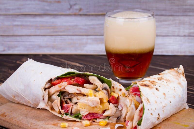 Burritos del pollo, del fungo, del formaggio e degli spinaci Vetro di birra fotografia stock libera da diritti