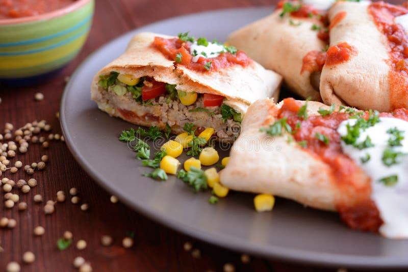Burritos mit Tacosoße und -Sauerrahm lizenzfreies stockfoto