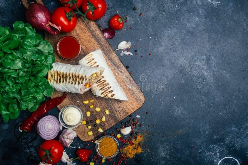 Burritosverpackungen mit gegrilltem Fleisch und Gemüse - Pfeffer, Tomaten und Mais stockfotografie