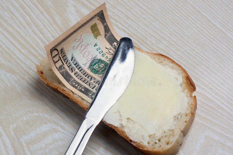 Burro e soldi su una fetta di pane fotografie stock libere da diritti
