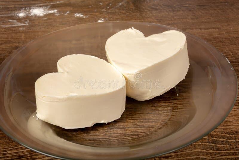 Burro o margarina bianco in forma di cuore in un piatto su una tavola di legno immagini stock