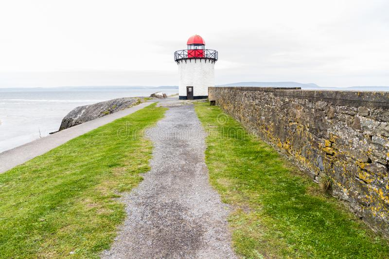 Burry port lighthouse. Small white squat white lighthouse with red top. Burry Port, Llanelli, Carmarthenshire, Wales royalty free stock image