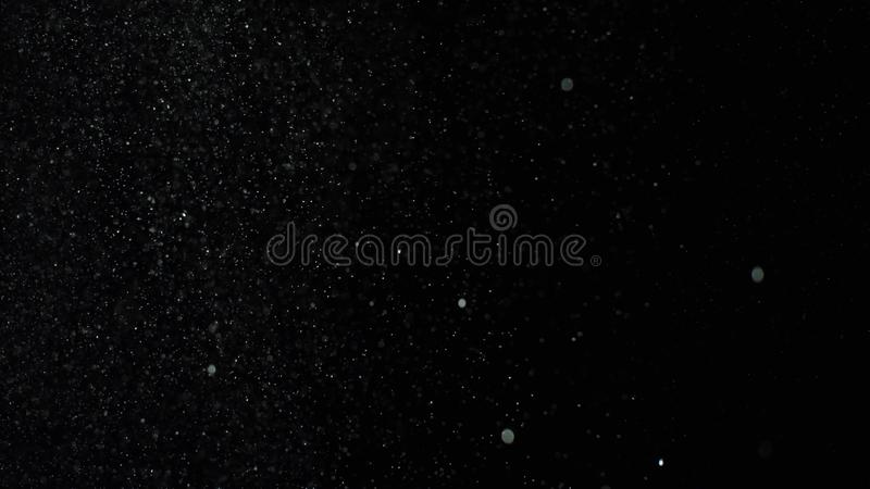 Bursts of white dust on black background. Stock footage. Explosion streams of white powder on black isolated background stock images