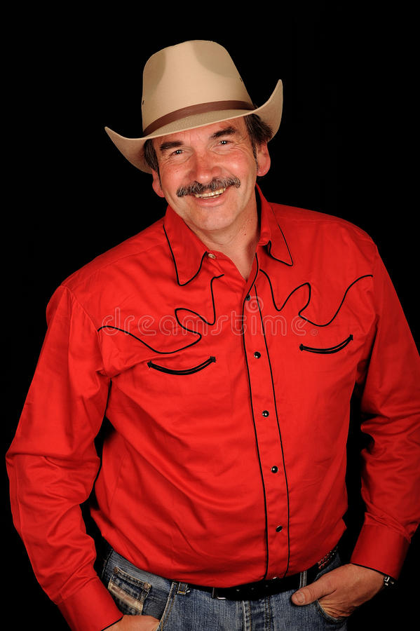 Burt Reynolds impersonator. Burt Reynolds celebrity look-a-like wearing a cowboy hat. Isolated against a black background stock photography