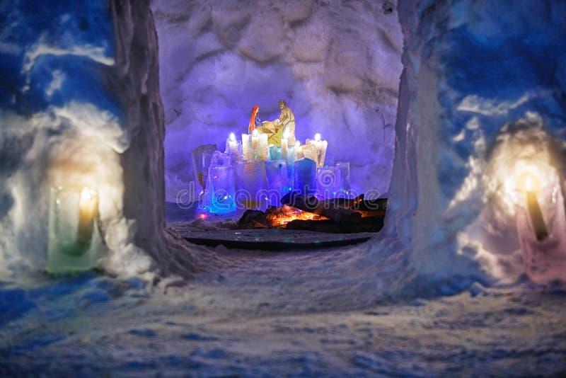 Burth внутренности установки Иисуса дома иглу снега с красочными ледяными plafonds и горящими свечами стоковые фото
