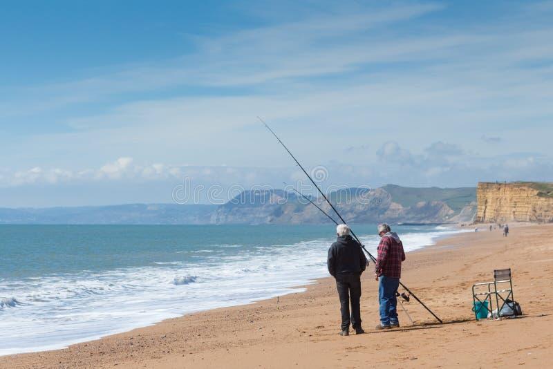 BURTON BRADSTOCK, UK - 12 ΑΠΡΙΛΊΟΥ 2016: Οι ψαράδες στέκονται στην παραλία στοκ εικόνα με δικαίωμα ελεύθερης χρήσης