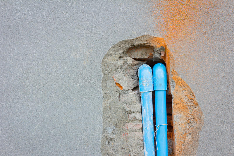 Bury a pvc pipe in the concrete wall with copyspace on the left. royalty free stock image