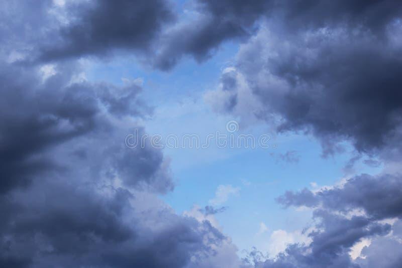 Burz chmury w niebieskiego nieba tle Ciemno?? i ?wiat?o, niebo zdjęcia stock
