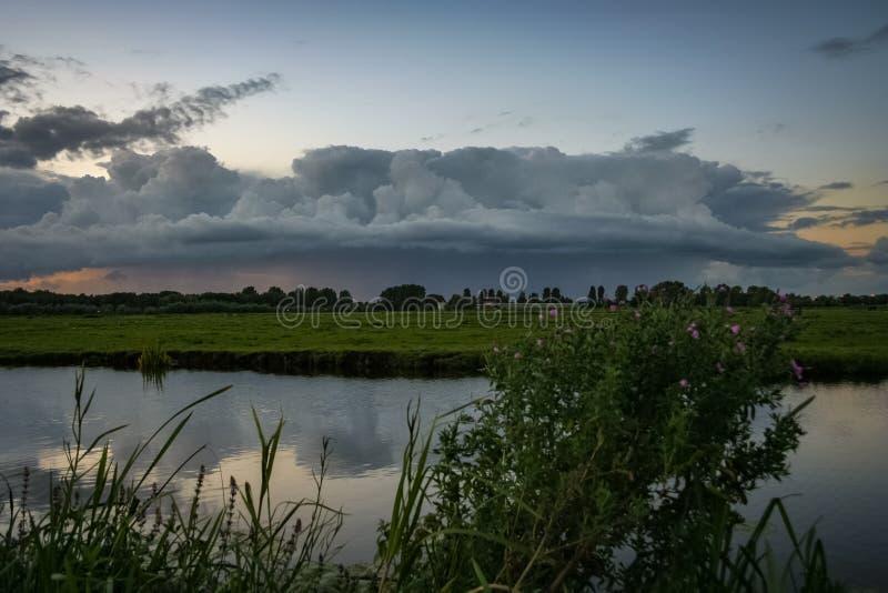 Burz chmury zbierają nad holenderskim polderu krajobrazem w zielonym sercu Holandia zdjęcia stock