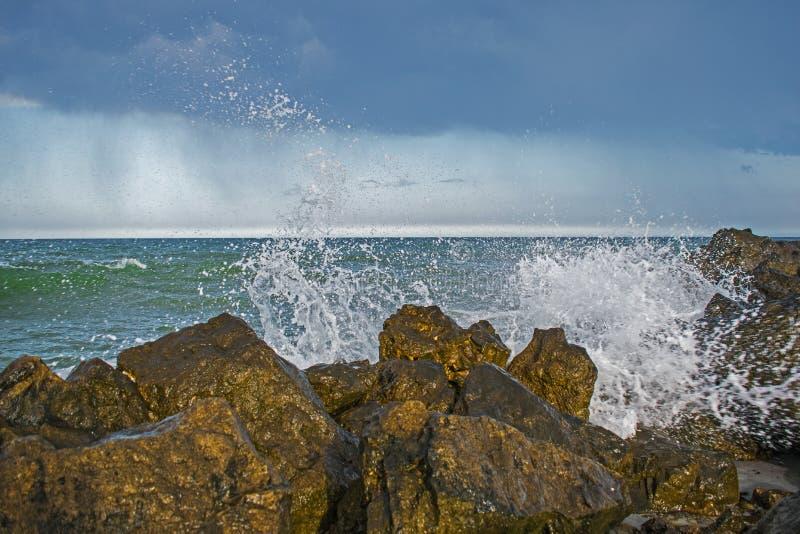 Burza zaczyna przy morzem fale uderzają skały i woda rozprasza niebo zakrywający z czarnymi chmurami zdjęcia stock