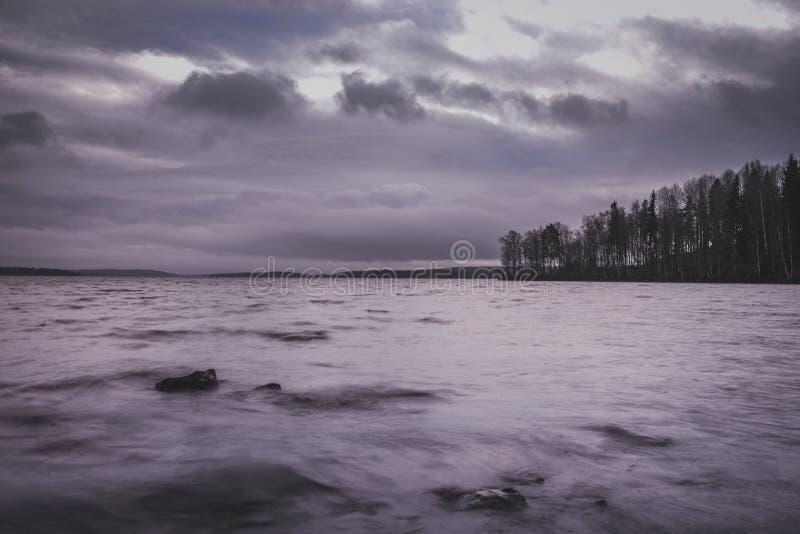 Burzowy jesieni jeziora wybrzeża widok z długim ujawnieniem obrazy stock