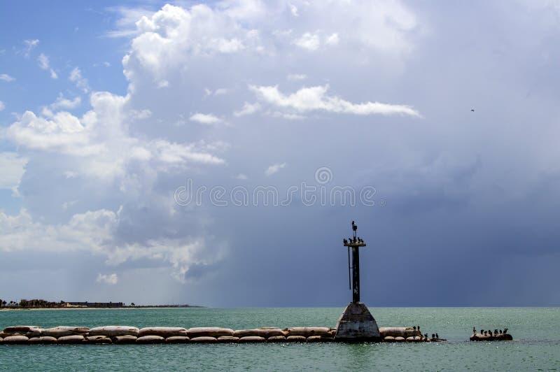 Burzowy niebo nad oceanem z falochronem robić torby rozciąga out z nieociosaną latarnią morską przy ptaka perc i końcówką beton fotografia stock