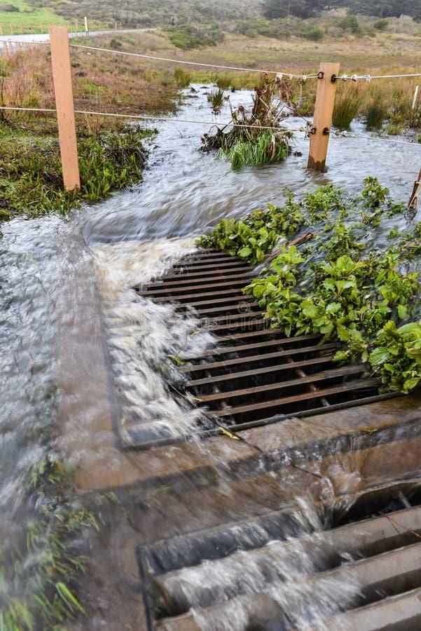 Burzy woda płynie w rynsztokową pobliską drogę zdjęcie royalty free