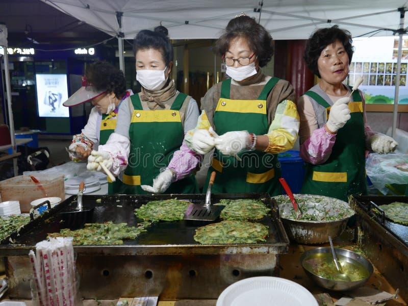 Busán, Corea 1 de mayo de 2017: La mujer hace las crepes coreanas imagenes de archivo