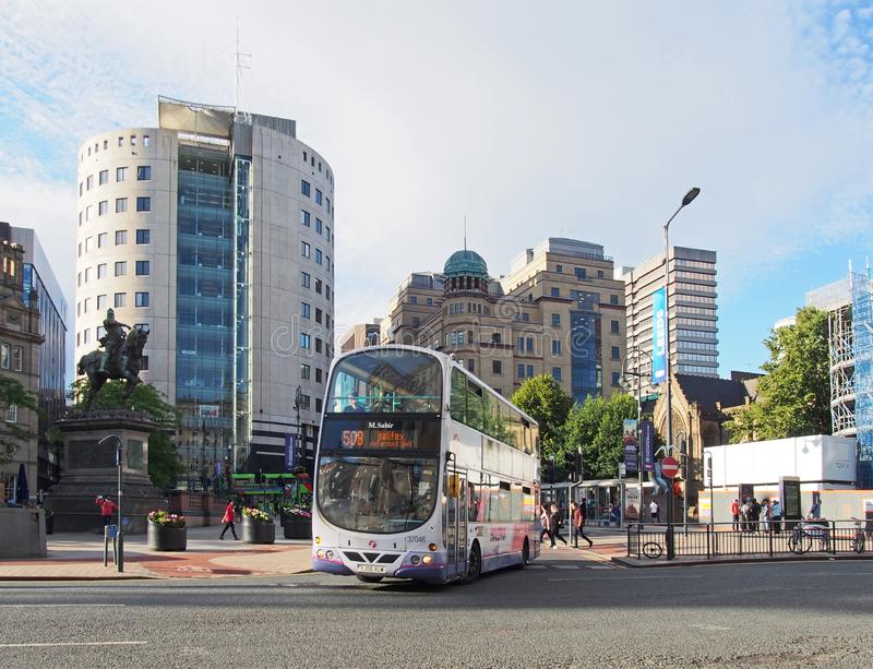 A bus in city square in leeds west yorkshire with people walking past city buildings and monuments in bright summer sunshine royalty free stock images