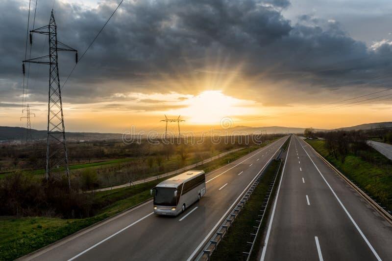 Bus, der auf eine einsame Landstraße reist lizenzfreie stockbilder
