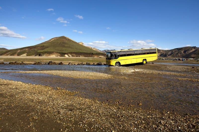 Bus, der einen Nebenfluss, Island kreuzt lizenzfreie stockfotografie