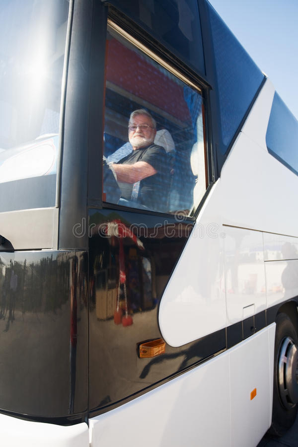 Bus Driver. Elderly tour bus driver at wheel, view through window royalty free stock photography