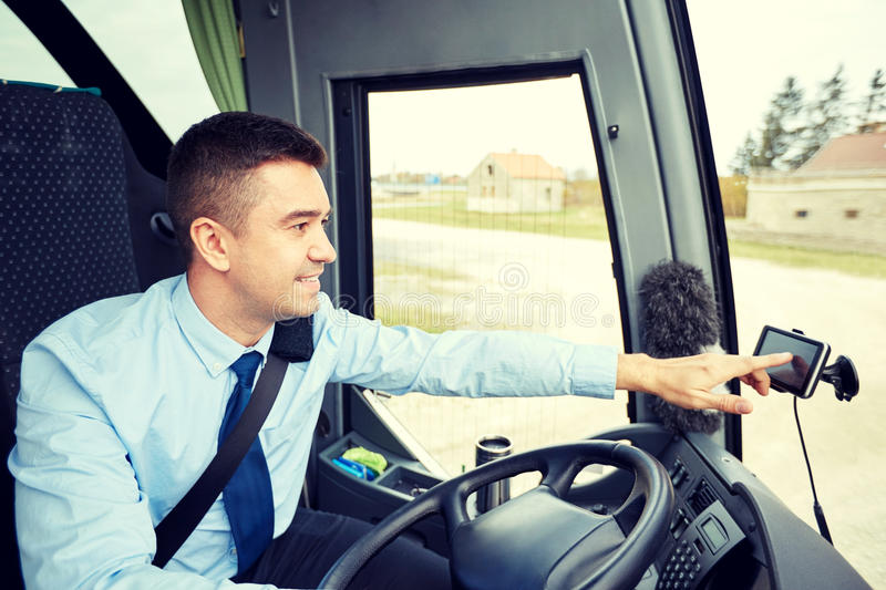 Bus driver entering address to gps navigator. Transport, transportation, navigation and people concept - bus driver entering address to gps navigator royalty free stock image