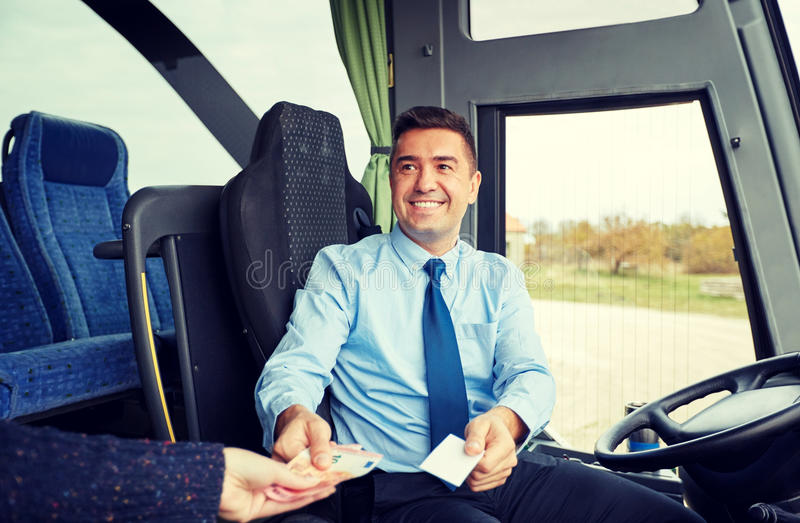 Bus driver with money selling ticket to passenger. Transport, tourism, road trip and people concept - smiling bus driver selling ticket and taking money from stock image