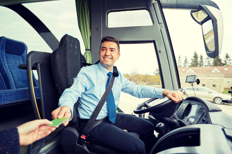 Bus driver taking ticket or card from passenger. Transport, tourism, road trip and people concept - smiling bus driver taking ticket or plastic card from royalty free stock photography