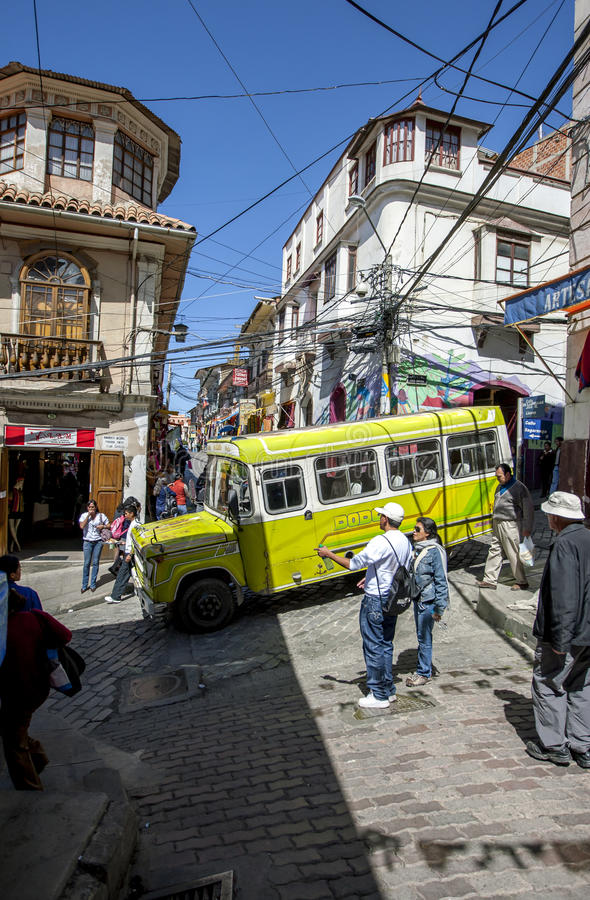 A bus drives down a steep and narrow street in Cerro Cumbre in La Paz in Bolivia. This suburb of La Paz is adjacent to the Witches' Market and has a chaotic royalty free stock photo