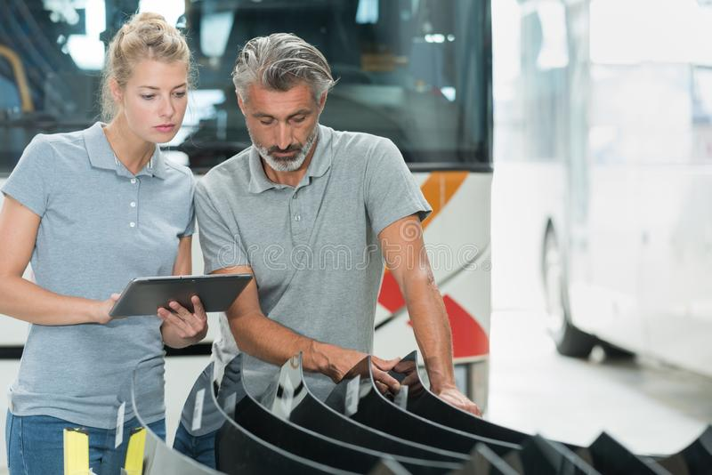 Bus factory technicians inspecting glass delivery. Glass royalty free stock photo
