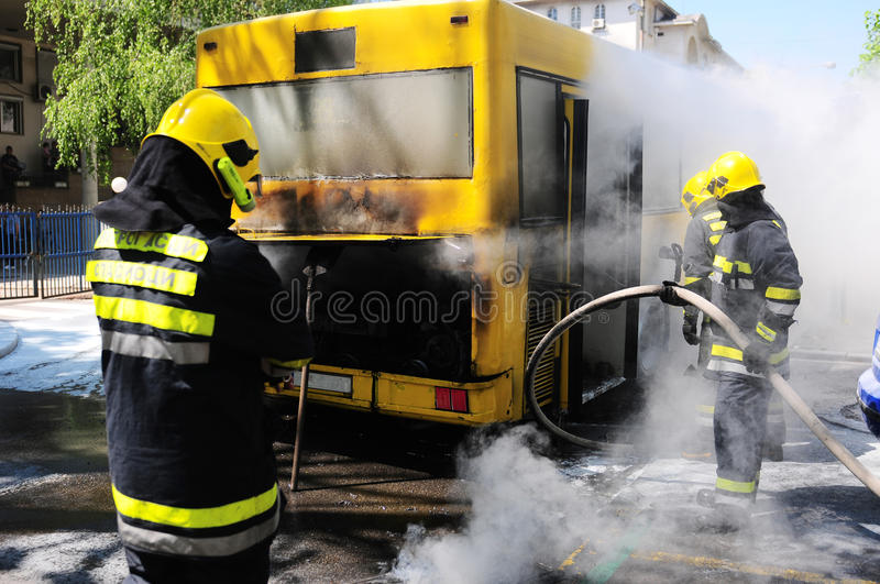 Bus on fire on the street. SERBIA, BELGRADE - APRIL 27, 2012: Fire fighters tries to extinguish burning bus on the street stock photos