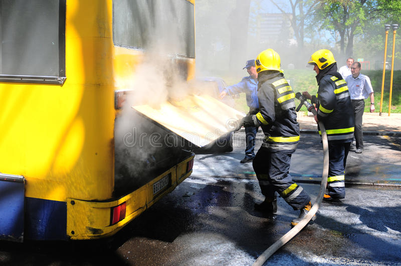 Bus on fire on the street. SERBIA, BELGRADE - APRIL 27, 2012: Fire fighters tries to extinguish burning bus on the street stock photography