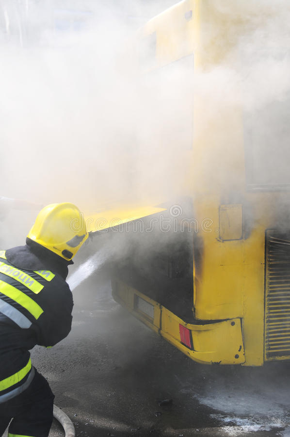 Bus on fire on the street in the middle of the day. SERBIA, BELGRADE - APRIL 27, 2012: Fire fighters tries to extinguish burning bus on the street royalty free stock image