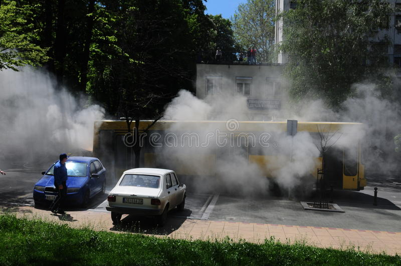 Bus on fire on the street in the middle of the day. SERBIA, BELGRADE - APRIL 27, 2012: Bus on fire on the street in the middle of the day. More than have of the stock photography
